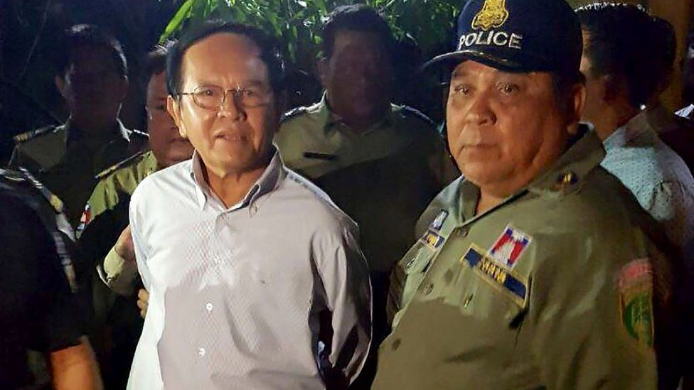 Cambodian opposition leader Kem Sokha (L) is escorted by police at his home in Phnom Penh on September 3, 2017.