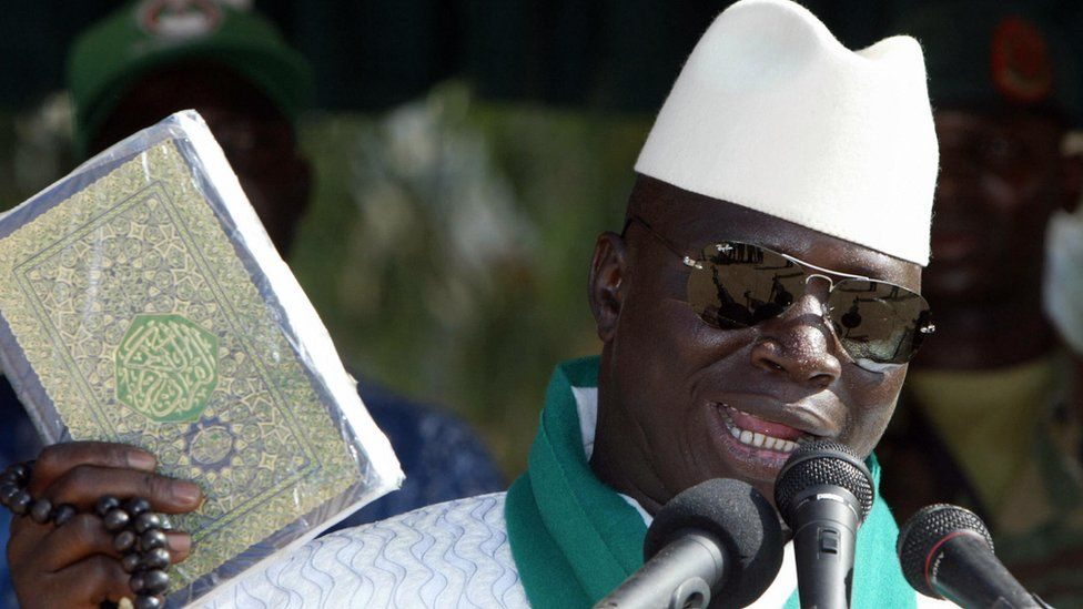 President Jammeh holds up a Koran while speaking into a microphone