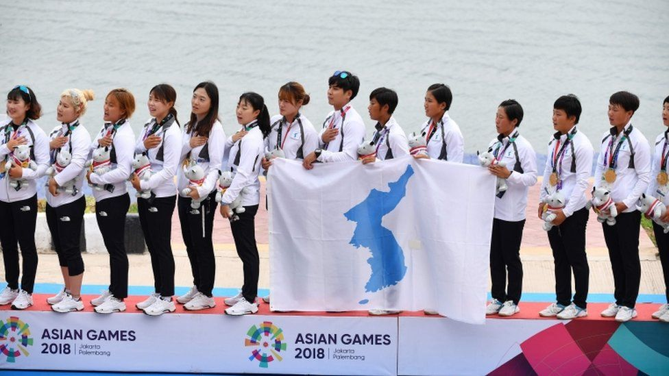 Unified Korea team sing together with unified flag