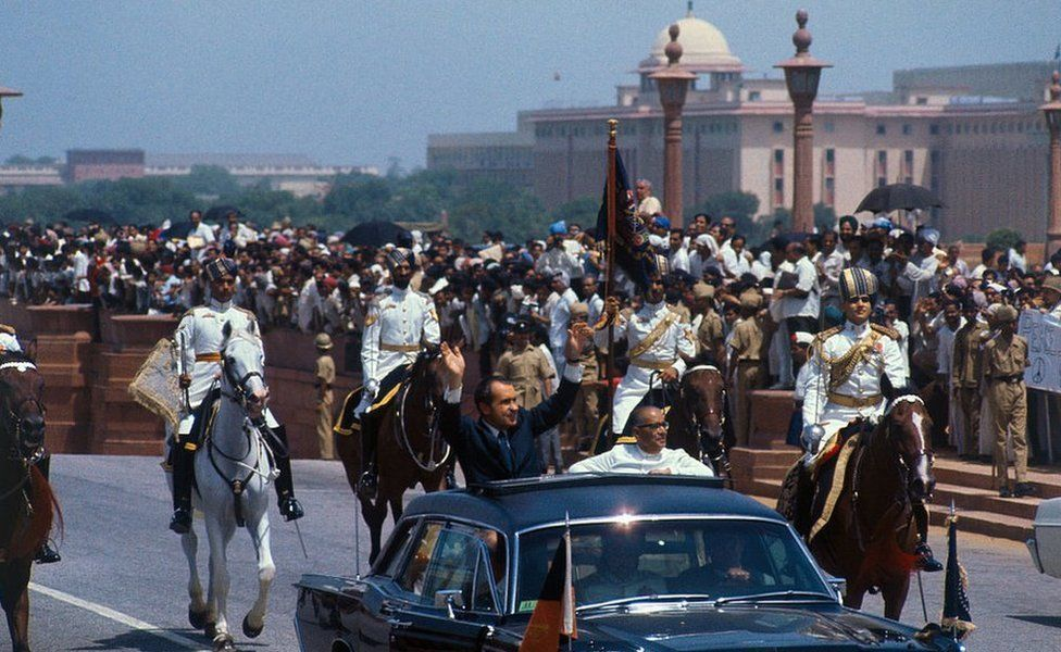 President Richard Nixon waves to crowds as he rides in open car with the acting president of India, Mohammad Hidyatullah, in motorcade from airport upon arrival here July 31.