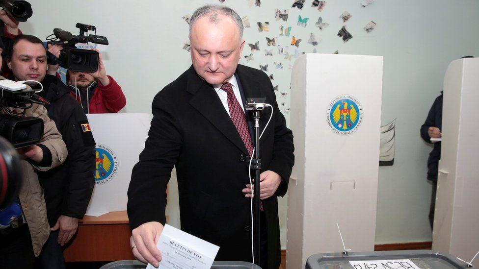 Igor Dodon, flanked by TV cameras, places his ballot paper into a ballot box