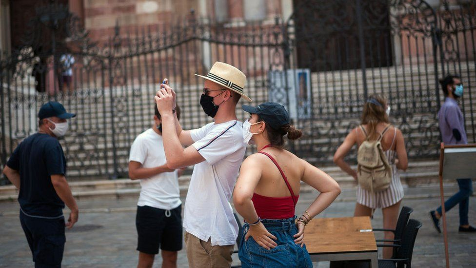 A tourist wearing a face mask takes photos at the Plaza del Obispo square in Malaga, Spain