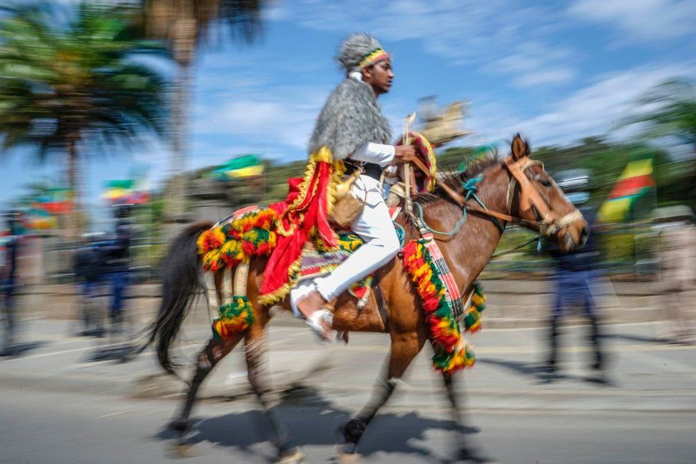 A man is seen riding a horse. Bother are wearing green, yellow and red colours for their symbolism.