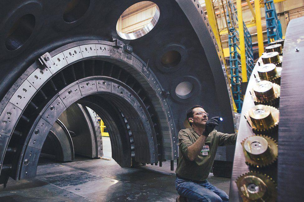 Engineer inspecting big machine parts