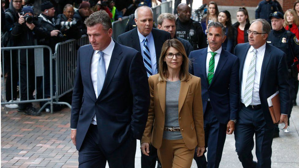 Actress Lori Loughlin, center in tan, and her husband Mossimo Giannulli, in green tie behind her, leave the John Joseph Moakley United States Courthouse in Boston on April 3, 2019