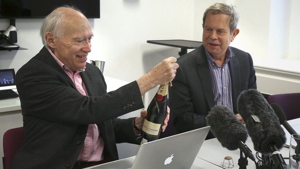scientists at desk with bottle of champagne