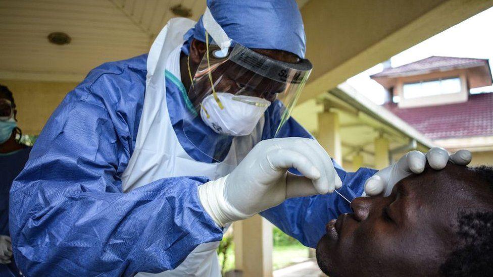 Coronavirus test sample being extracted by lab worker in Kisumu