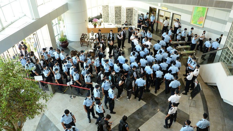 A handout photo made available by Apple Daily shows police officers arriving at the office of Next Media