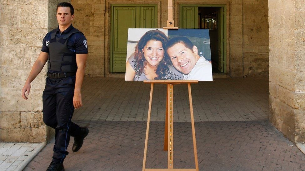 A policeman walks past a photograph of French policeman Jean-Baptiste Salvaing and his partner Jessica Schneider after a memorial ceremony in the city of Pezenas, France, 20 June 2016.