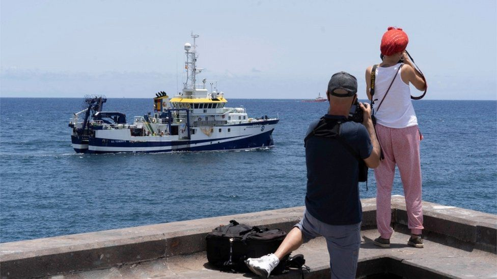 The oceanographic vessel Angeles Alvarino with two people taking a photo of it on the shore