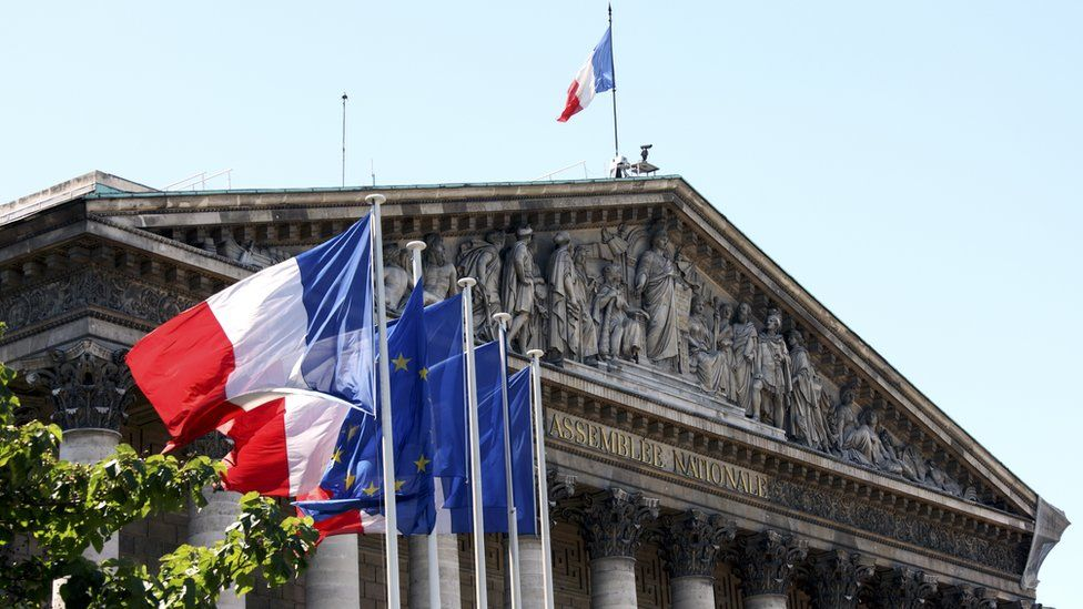 French flags fly outside the National Assembly in Paris