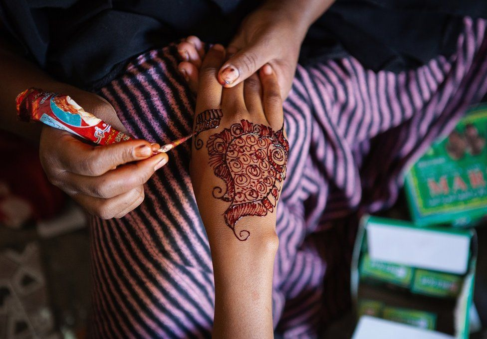 Hand being painted with henna