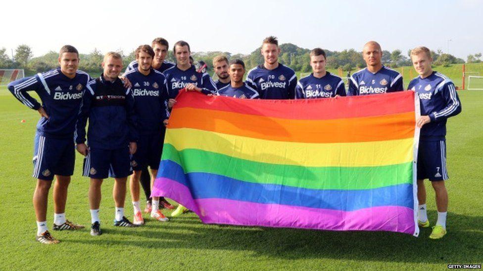 Sunderland players hold up a rainbow flag
