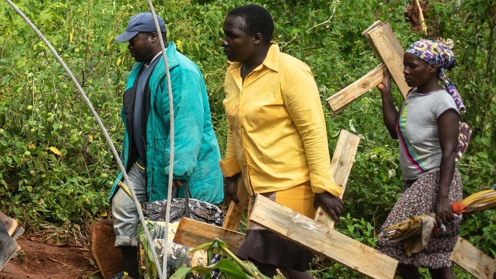 People carrying crosses in Chimanami at bodies are buried after Cyclone Idai