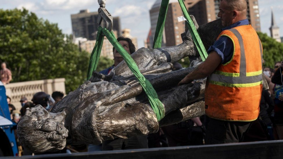A statue of Christopher Columbus, which was toppled by protesters, is loaded onto a truck in St Paul, Minnesota