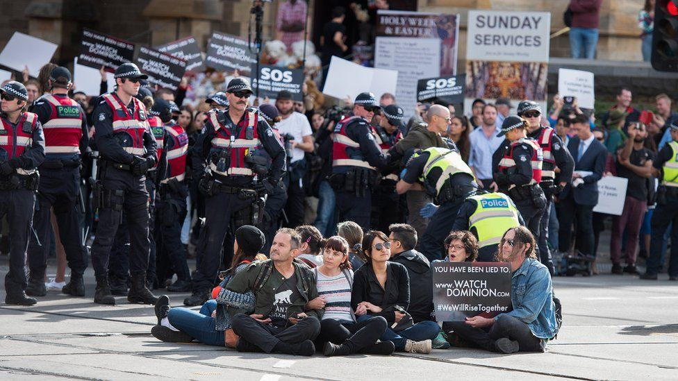 Police move in on animal rights protesters sitting on roads in the middle of Melbourne