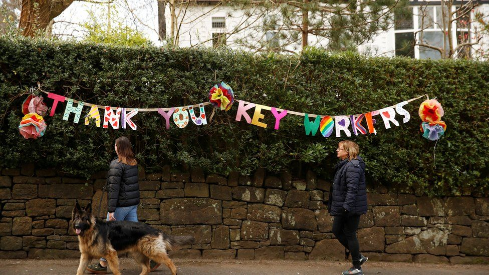 "People walk past a banner reading ""Thank you key workers"", as the spread of the coronavirus disease (COVID-19) continues, Manchester"
