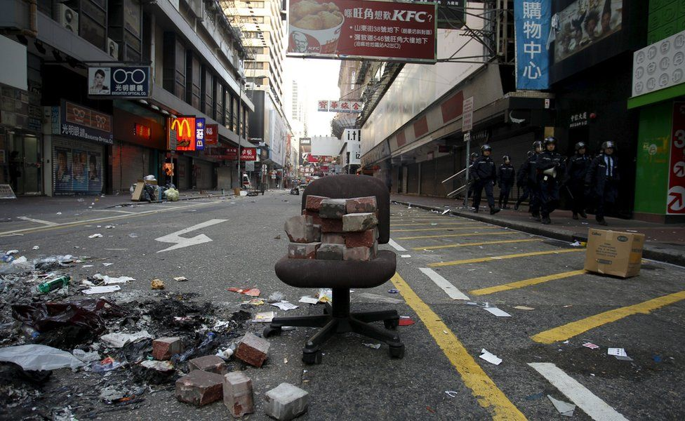 Chair in deserted street, with bricks stacked up on top