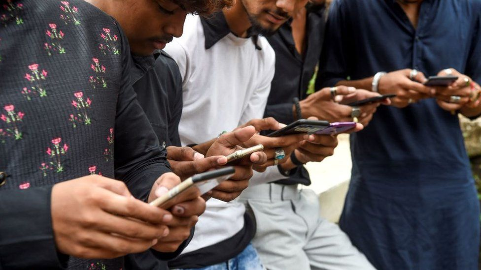Youngsters watch videos on video-sharing app TikTok on their mobile phones