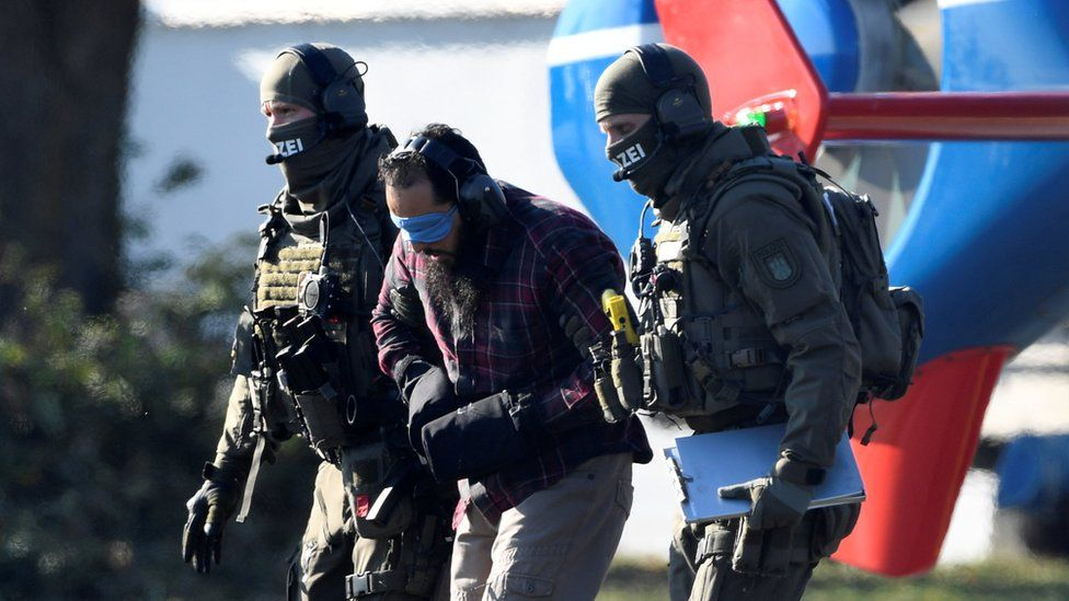 A bearded man, blindfolded, with ear protectors and his hands bound in heavy mitts, is escorted by heavily armed police in full tactical gear, faces hidden by balaclavas