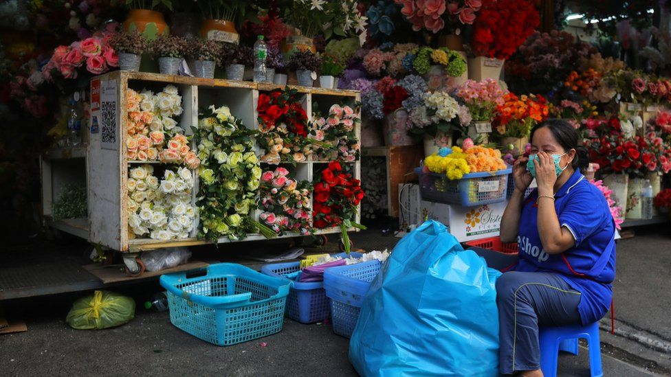 A woman wearing a mask while working on a flower stall in Bangkok, Thailand