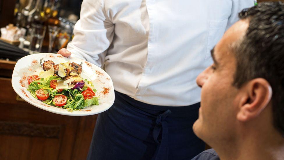 Waiter showing food to diner (stock shot)