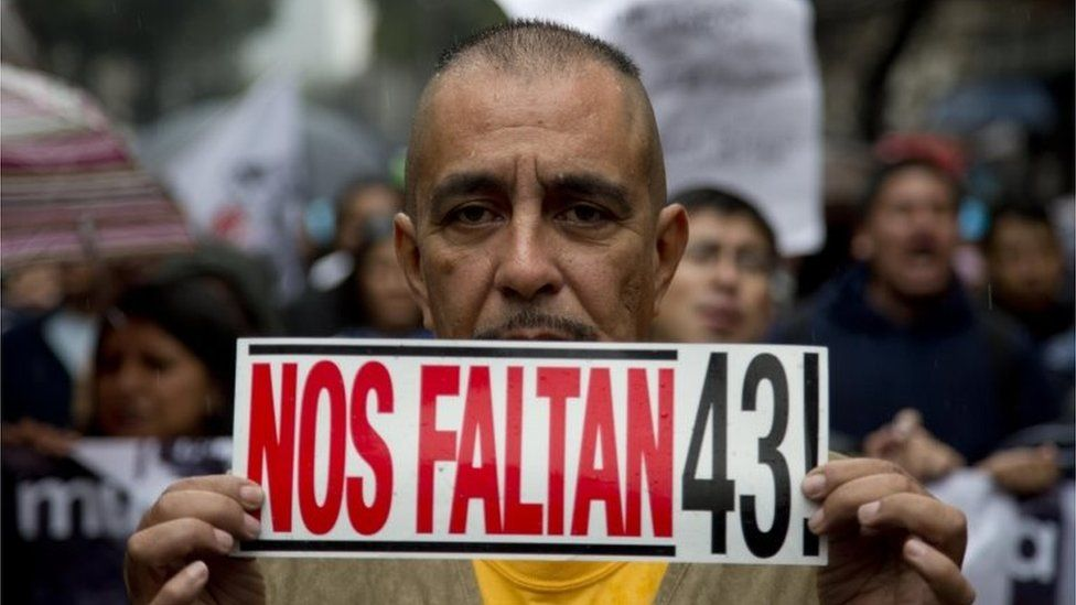 """A man holds a sign that reads in Spanish: """"We""""re missing 43"""" during a march marking the one year anniversary of the disappearances of 43 college students in Mexico City on 26 September 2015"""