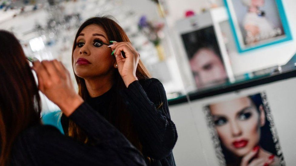 Mexican transgender mayoral candidate for Zatelco, Valeria Lorety, is reflected on a mirror as she puts makes up at her beauty salon on in Zacatelco, Tlaxcala state, Mexico, on 27 April 2021.