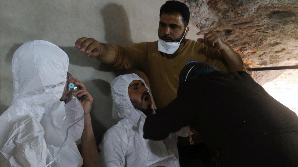A man breathes through an oxygen mask as another receives treatment after what rescue workers described as a suspected chemical attack in the town of Khan Sheikhoun in rebel-held Idlib, 4 April 2017