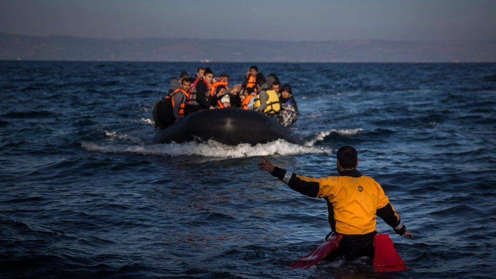 Volunteer lifeguard shows the way to a migrant boat off Lesbos (26 December)