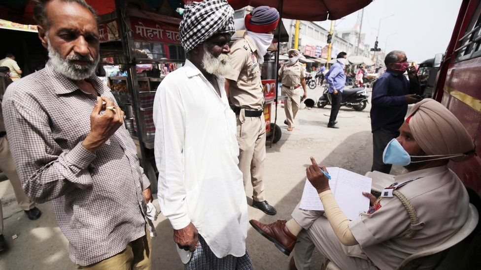 An Indian police officer (R), notes down details of defaulters who are not wearing face masks before testing them for Covid19 disease, in a mobile van set up to test random people who are not wearing the mandatory face masks, in Amritsar, India, 25 March 2021