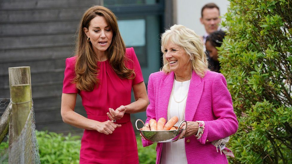 Catherine and Dr Biden walking along talking while the First Lady holds a bowl of carrots