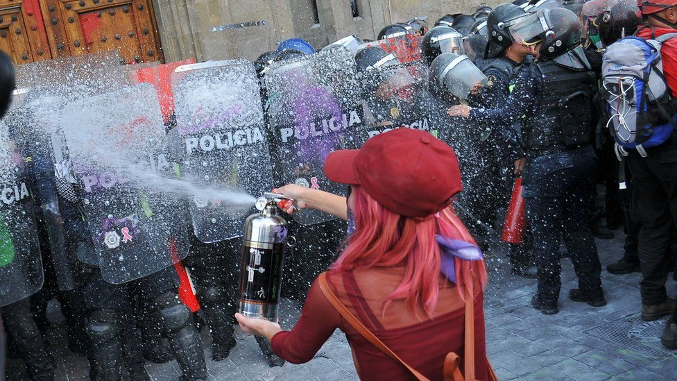 A woman faces the police while taking part in a protest during the International Women's Day in Mexico City