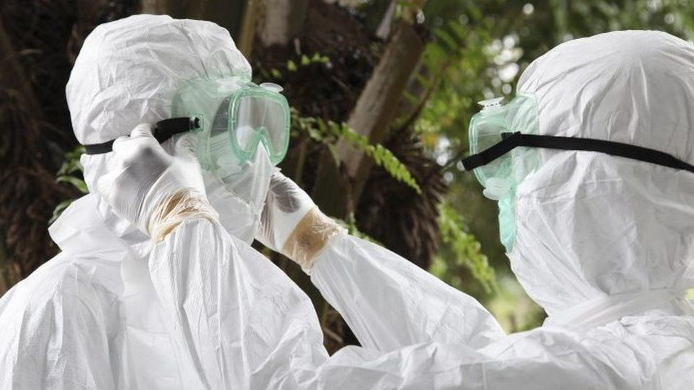 Liberian nurses put on protective clothing as preparation to carry the body of an Ebola victim for burial (08 August 2014)
