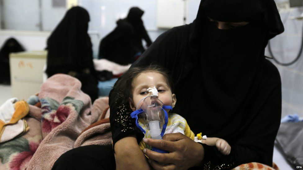 A Yemeni woman helps her malnourished child to breathe at a therapeutic feeding centre in a hospital in Sanaa on 12 August 2015
