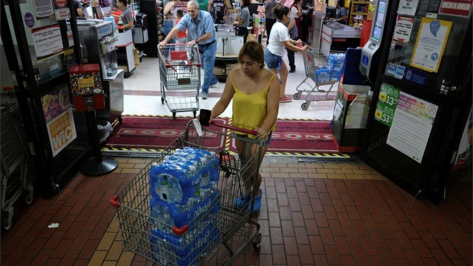 A woman purchases bottled water from a local grocery store as Tropical Storm Dorian approaches in Cabo Rojo, Puerto Rico