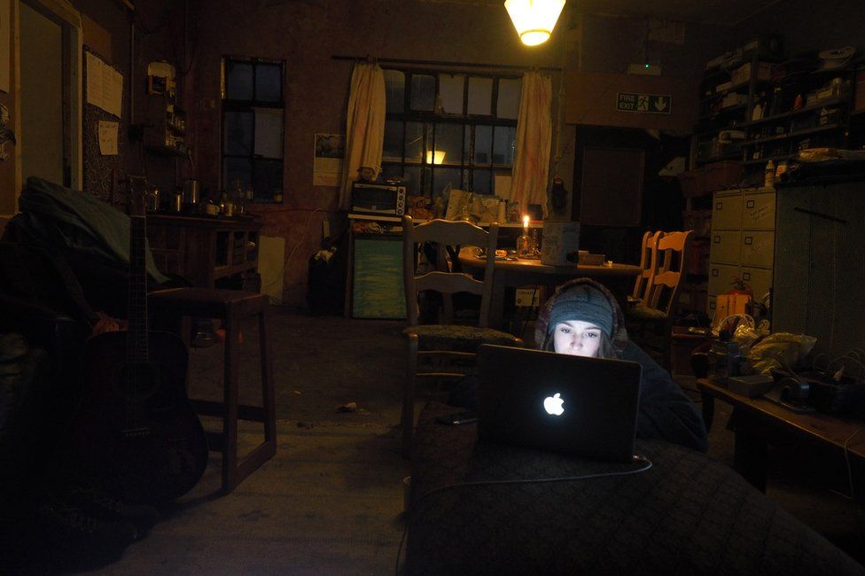 A woman using a laptop in a darkened room