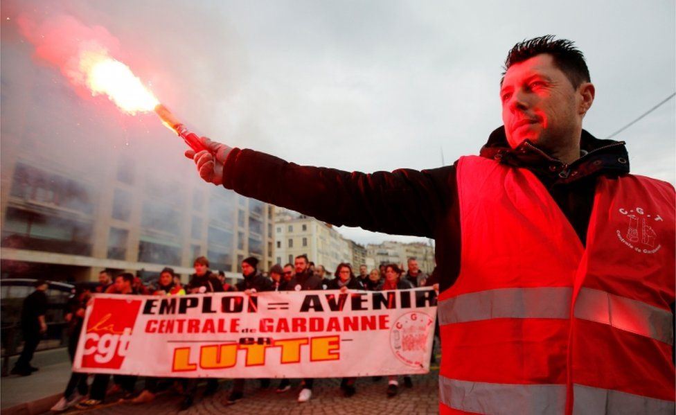 A protester holds up a flare as French Labour unions members demonstrate against the French government's pensions reform plans in Marseille