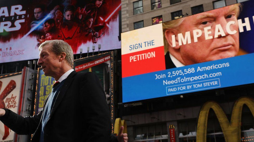 Philanthropist Tom Steyer stands near a billboard promoting his petition to impeach Donald Trump in New York.