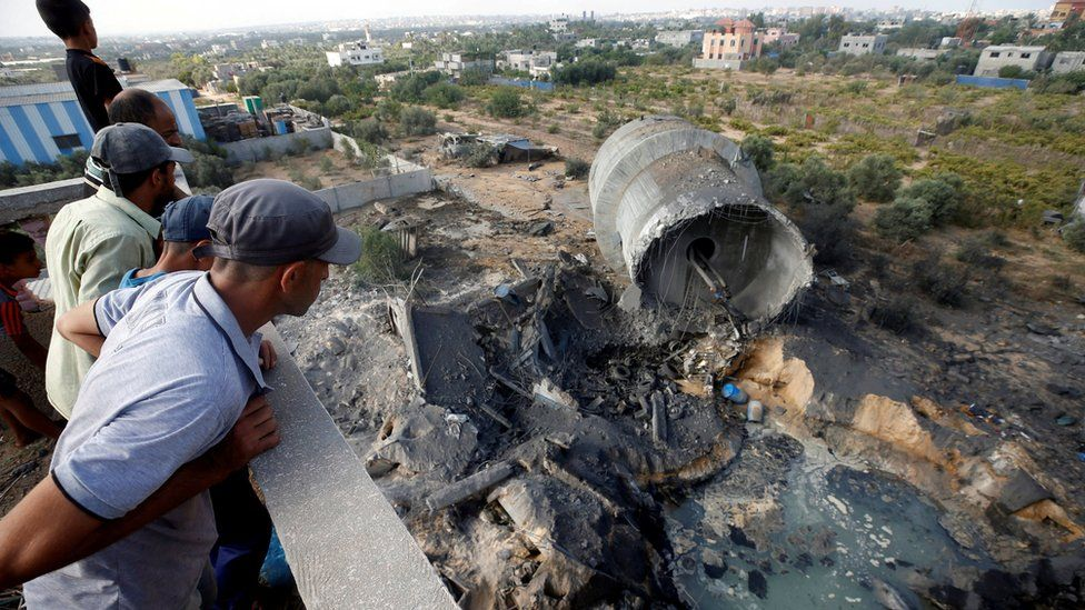 Palestinians look at damage at the site of an Israeli air strike on the outskirts of Gaza City (9 August 2018)