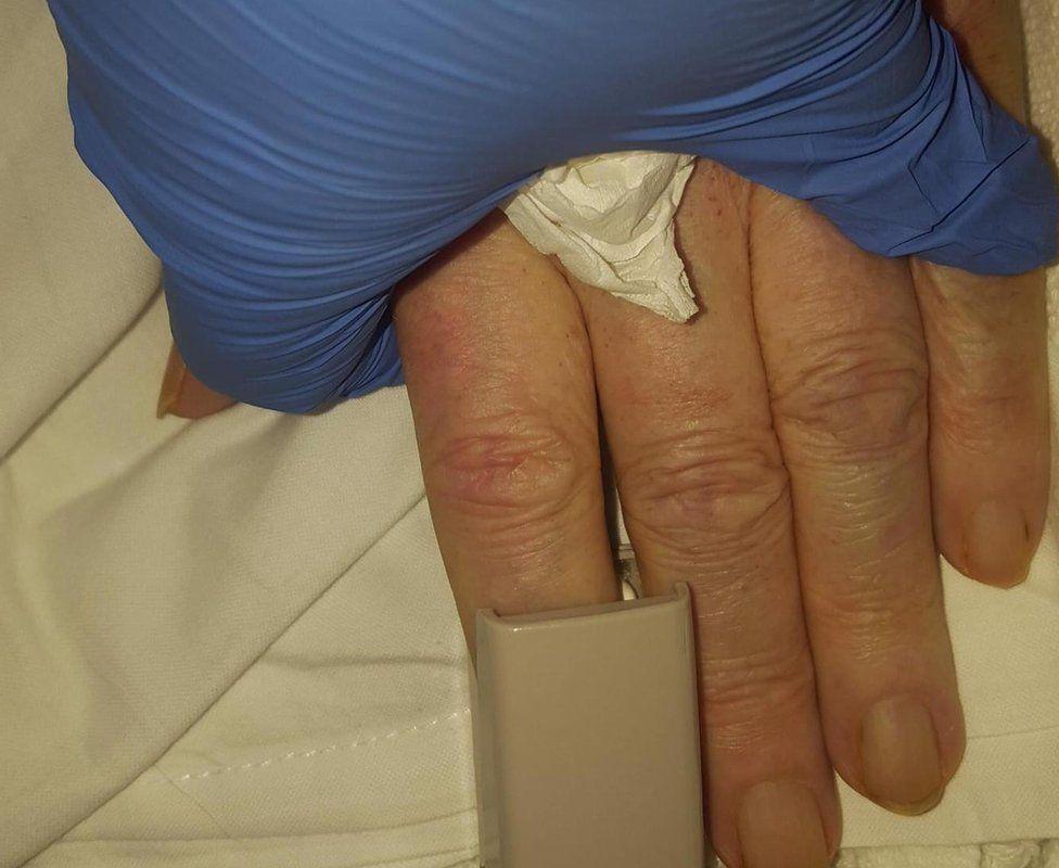 Joanna holds Keith's hand in hospital