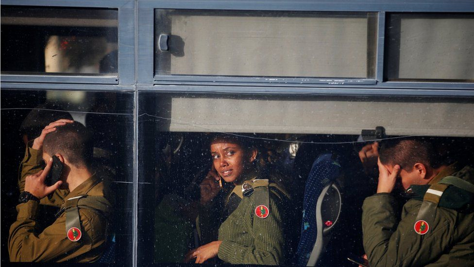 Israeli soldiers sit in a bus as they leave the scene of a truck-ramming incident in Jerusalem January 8, 2017.
