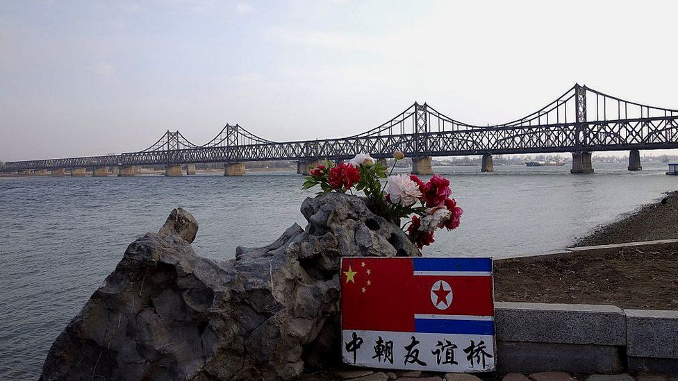 A sign displaying the Chinese (L) and North Korean (R) flags is pictured beside the Sino-Korean Friendship Bridge which leads to the North Korean town of Sinuiju, on the banks of the Yalu River, in Dandong, northeastern Liaoning province