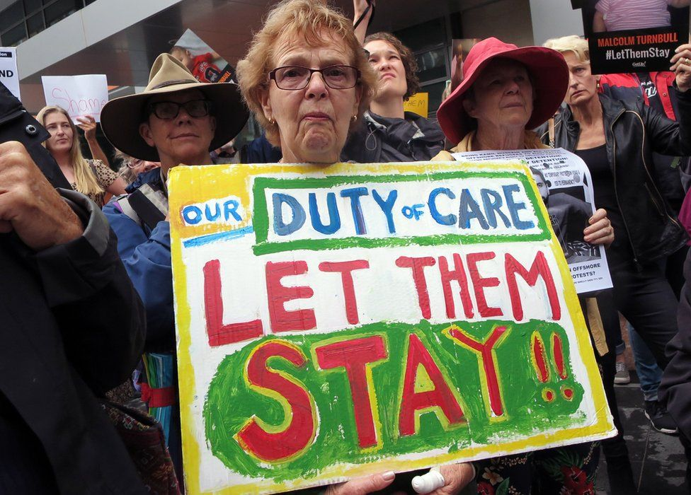 """A woman protesting Australia's offshore detention policy holds a placard saying """"Our duty of care: let them stay"""""""