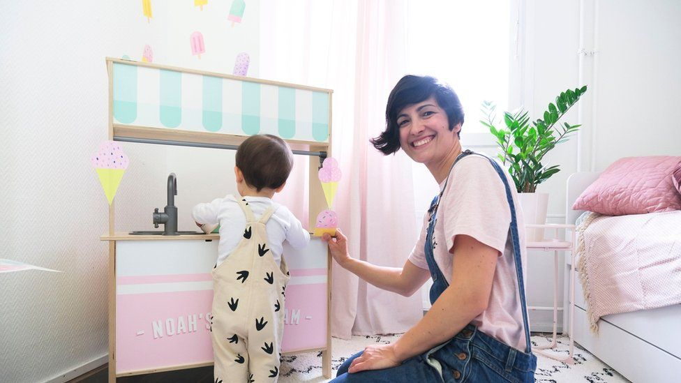 A woman and a child standing next to the wall sticker