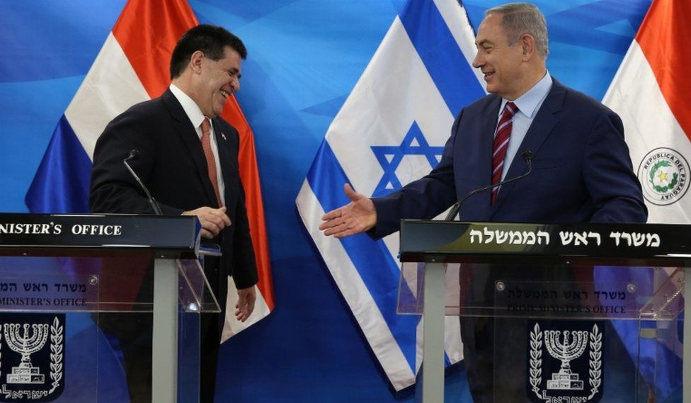 Israel's Prime Minister Benjamin Netanyahu reaches out to shake hands with Paraguayan President Horacio Cartes