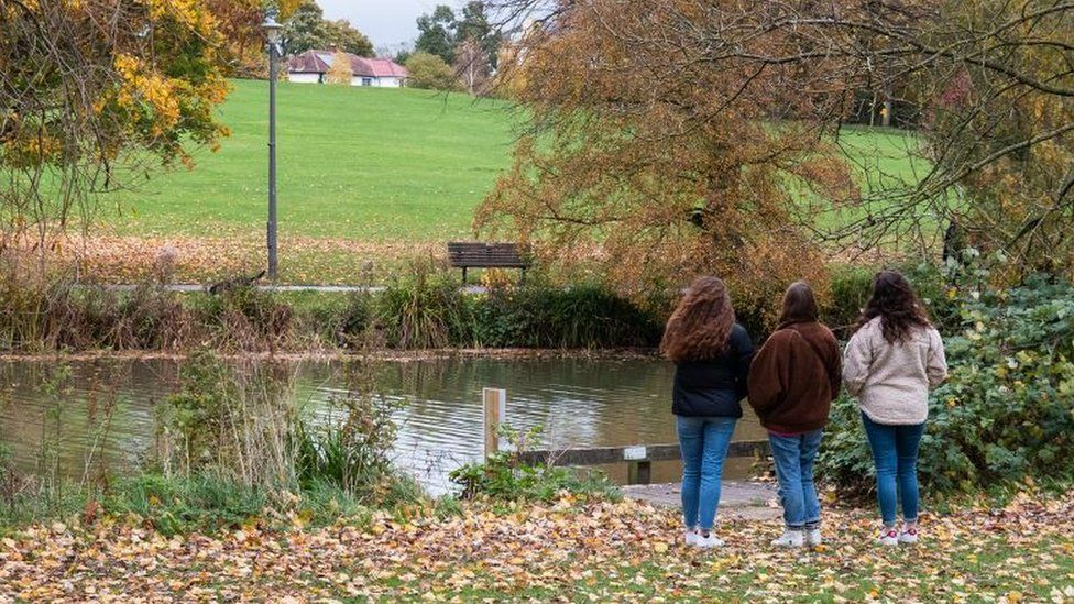 Three young women in a park are seen looking across a stretch of water towards a park bench
