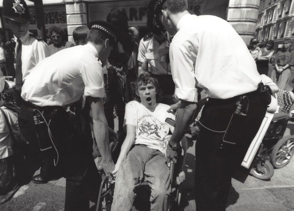 Wheelchair user being lifted by police