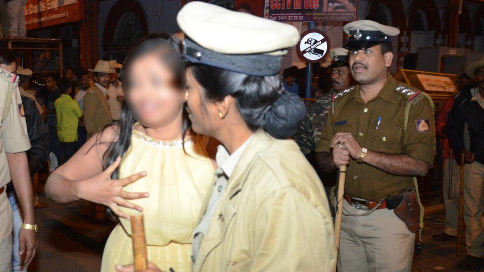 A weeping woman seeks help from a policewoman