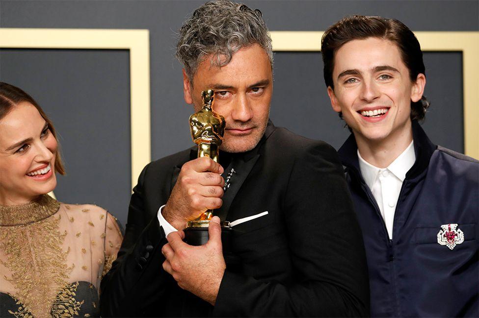 Taika Waititi holds his Oscar
